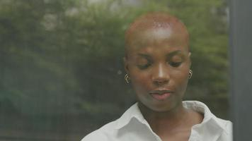 Young woman with shaved hair working by window