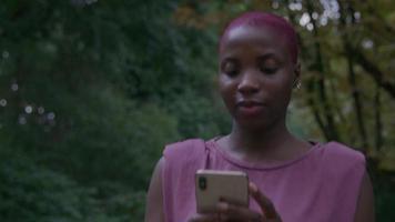 Cámara lenta de mujer joven caminando en el parque con teléfono video