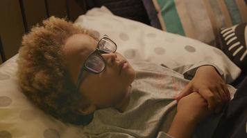 Young boy wearing glasses lying in bed