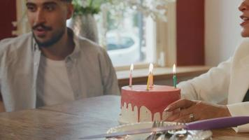 Boy blowing out candles on cake with family watching