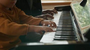Incline hacia arriba del hombre maduro enseñando piano de nieto