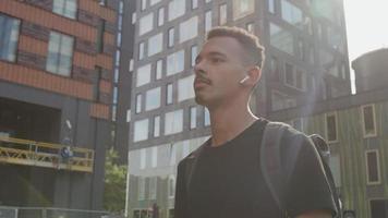 cámara lenta de hombre joven caminando en la ciudad con auriculares