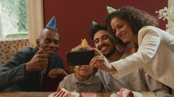 Multiethnic family celebrating boy's birthday taking photo on phone