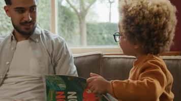 niño leyendo un libro al padre en casa