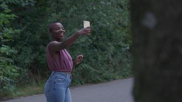 Young woman taking selfie in park