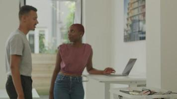 mujer joven, usar la computadora portátil, y, discutir, con, colega masculino