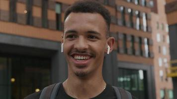 Slow motion of young man wearing wireless ear pods laughing