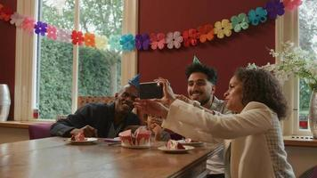 Family taking selfie on phone at boy's birthday party