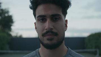 joven con bigote y barba mirando a la cámara