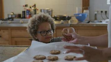 Mother giving freshly baked cookie to son