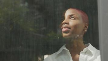 Young woman with shaved hair looking through window