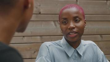 Young woman with shaved pink hair talking to colleague