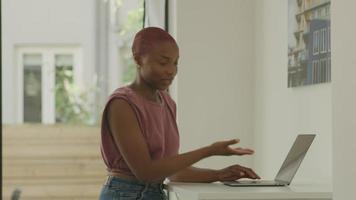 Mujer joven con portátil con ayuda de colega masculino
