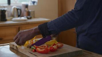 homem maduro cortando pimenta fresca