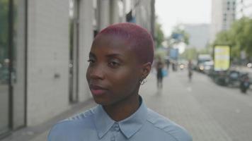 câmera lenta de uma jovem com cabelo raspado andando na calçada