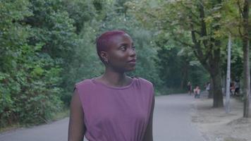 junge Frau mit rasierten Haaren im Park video