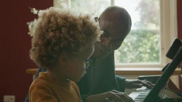 homem maduro ensinando piano ao neto