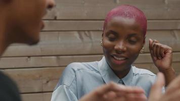 Mujer joven con cabello rosado afeitado escuchando a un colega