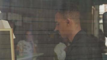 jeune homme travaillant, vue à travers la fenêtre video