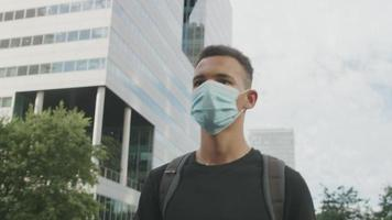 Zeitlupe des jungen Mannes, der schützende Gesichtsmaske in Stadt trägt video