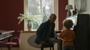 Mature man by piano with grandson