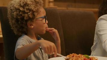 Boy wearing glasses enjoying pasta at dinner