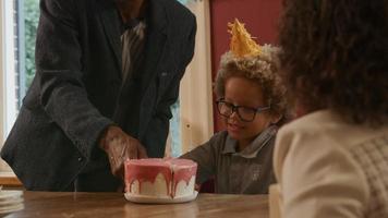 abuelo ayudando a su nieto a cortar el pastel de cumpleaños