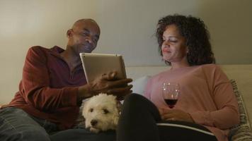 casal maduro com cachorro relaxando no sofá em casa
