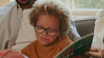 menino lendo livro com os pais em casa