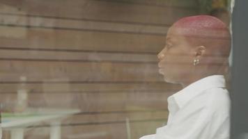 jovem mulher com cabelo raspado trabalhando perto da janela