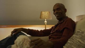 homem maduro no sofá acariciando cachorro de estimação video