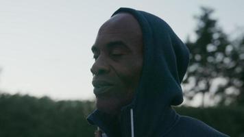 homem maduro vestindo blusa com capuz olhando para a câmera