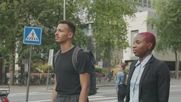 Slow motion of young man and woman waiting to cross street video