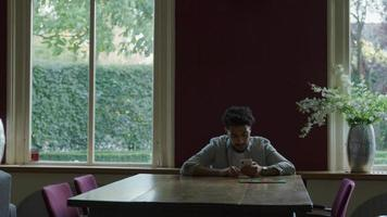 joven, utilizar, teléfono, en, mesa de comedor