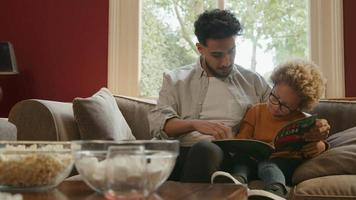 padre, libro de lectura, con, hijo, en, sofá, en casa