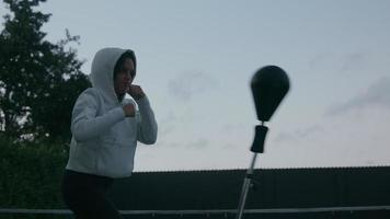 Mujer madura vistiendo la parte superior con capucha con punch ball