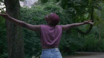 cámara lenta de mujer joven en el parque con los brazos extendidos