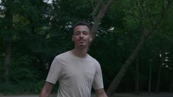 Slow motion of young man walking in park looking at camera
