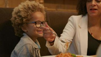 madre alimentando a su hijo pasta fresca cocida en la cena