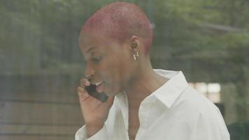 jovem mulher com cabelo raspado falando ao telefone video