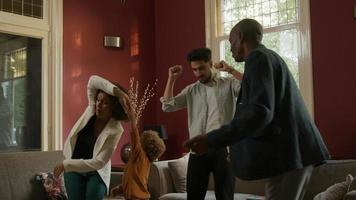 Slow motion of multiethnic family dancing together at home