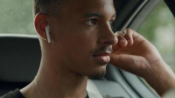 Young man sitting in back of cab wearing ear phones