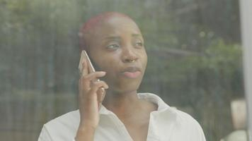 Young woman with shaved hair talking on phone