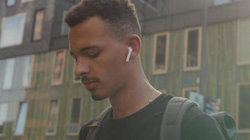 rallentatore inclinazione verso l'alto del giovane utilizzando smartphone indossando baccelli auricolari video