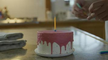 Person putting candles in birthday cake