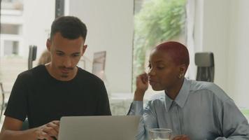 hombre y mujer joven, usar la computadora portátil, en, oficina video