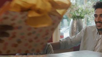 niño con gorro de fiesta abriendo regalo de cumpleaños