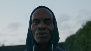 Mature man wearing hooded top looking at camera