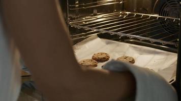 Galletas recién horneadas que se retiran del horno con joven viendo video