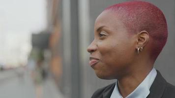 joven empresaria con cabello rosado afeitado hablando